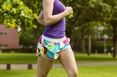 Side view mid section of healthy and beautiful young woman jogging in park