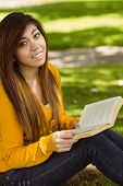 Portrait of relaxed female college student reading book in the park