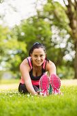 Athletic brunette stretching on the grass in the park