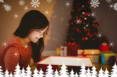 Little girl opening a glowing christmas gift against fir tree forest and snowflakes