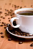foto of cup coffee  - cup of coffee and beans on wooden table - JPG