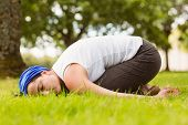 Brunette relaxing and meditating on grass in the park