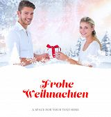 young couple with gift against christmas greeting in german