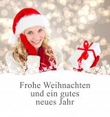 happy festive blonde with gift against christmas greeting in german