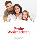 Parents offering a gift to their daughter against christmas greeting in german