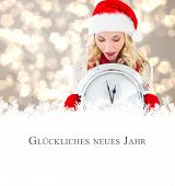 happy festive blonde with clock against christmas greeting in german