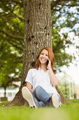 Pretty redhead smiling on the phone in park on a sunny day