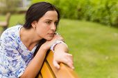 Thoughtful brunette sitting on bench in the park