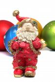 Small Ceramic Santa Claus On A Background Of Christmas Toys