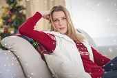 Cute blonde sitting on couch posing against twinkling stars