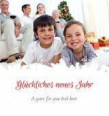Smiling children looking for presents in Christmas boots against christmas greeting in german