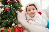 Cute baby boy on couch at christmas against snow