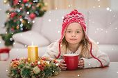 Cute little girl holding mug at Christmas against snow