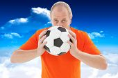 Nervous football fan holding ball against bright blue sky with clouds