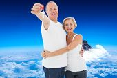 Mature couple smiling at camera with new house key against mountain peak through the clouds