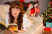 Pretty woman lying on a cosy couch reading book at christmas at home in the living room