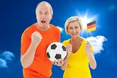 Happy german couple cheering at camera holding ball against bright blue sky with clouds