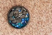 Pearls And Colored Stones In Clay Vase On Carpet Background.