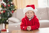Festive little boy smiling at camera against snow