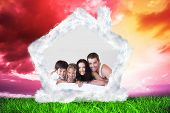 Lovely family lying on their bed against green grass under red and purple sky