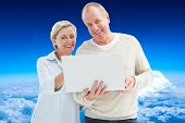 Happy mature couple using laptop against mountain peak through the clouds