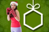 Festive brunette in boxing gloves against blurred christmas background