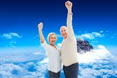 Happy mature couple cheering at camera against mountain peak through clouds