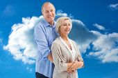 Happy mature couple embracing each other against cloudy sky