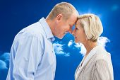 Happy mature couple facing each other against bright blue sky with clouds