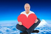 Upset man sitting holding heart shape against mountain peak through the clouds