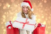 Woman in santa hat offering a gift against yellow abstract light spot design
