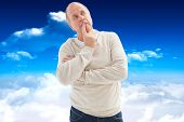 Thinking mature man with hand on chin against bright blue sky with clouds