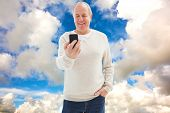 Happy mature man sending a text against blue sky with white clouds