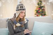 Pretty blonde with winter hat on writing on her notebook against snowflakes