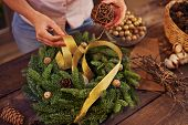 Female hands decorating xmas wreath with golden ribbon