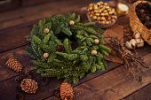 Coniferous wreath on wooden table with cones near by