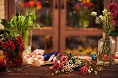 Flowers, berries and decorative ribbons on workplace of florist