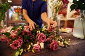 Female florist separating roses from small white flowers in workshop
