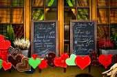 image of alsatian  - Menu boards in window with heart decorations in Alsace - JPG