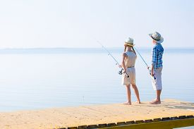 picture of rod  - Boy and girl with fishing rods fishing together from a pier - JPG