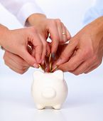foto of coin slot  - Putting coin into the piggy bank  - JPG