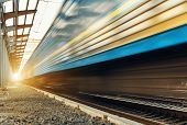 picture of passenger train  - High speed passenger train on tracks with motion blur effect at sunset - JPG