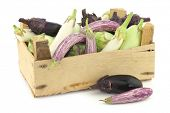 stock photo of wooden crate  - fresh mixed aubergines - JPG