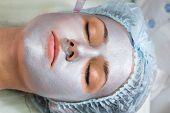 pic of face mask  - Beautician working on a face model in a spa salon - JPG