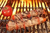 stock photo of kababs  - Two Roasted BBQ Beef Kababs And Tomato On The Hot Flaming Grill Close - JPG