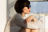 pic of daydreaming  - Girl with sunglasses daydreaming sitting by the window - JPG