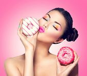 foto of high calorie foods  - Beauty fashion model girl taking kissing colorful donuts - JPG