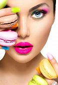 stock photo of slim model  - Beauty fashion model girl with colourful makeup and manicure taking colorful macaroons - JPG