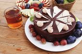 foto of cream cake  - whole big chocolate cream brownie cake topped with white chocolate and cream flowers with hot tea cup decorated with fruits apple plum and grape on plate on wooden table - JPG