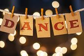 stock photo of congas  - The word DANCE printed on clothespin clipped cards in front of defocused glowing lights. ** Note: Visible grain at 100%, best at smaller sizes - JPG